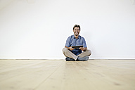 Mature man sitting on ground in empty room, using digital tablet - PDF01387