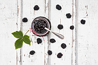 Glass of homemade blackberry jam, blackberries and leaf on wood - LVF06289