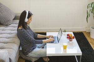 Young woman using laptop and headphones at home - MOMF00252