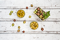 Cardboard box of gooseberries and jars of preserved gooseberries on wood - LVF06292