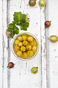Jar of preserved gooseberries and gooseberries on wood - LVF06295