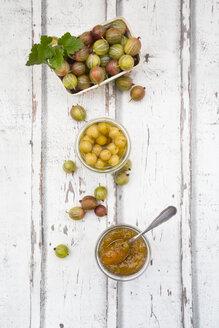 Cardboard box of gooseberries and jars of gooseberry jam and preserved gooseberries on wood - LVF06298