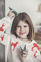 Portrait of smiling little girl with miniature Christmas trees - RTBF01031