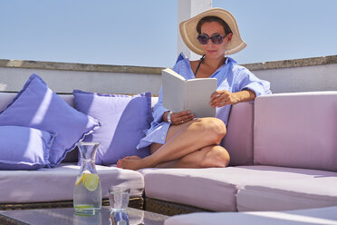 Woman with book relaxing on sun deck - DIKF00286