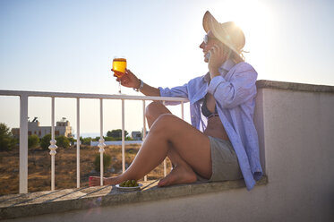 Woman with glass of spritz on cell phone on balcony - DIKF00289