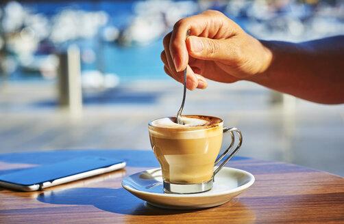 Close-up of woman's hand stirring glass of Espresso Macchiato - DIKF00292