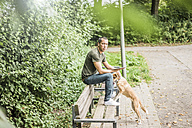Portrait of serious man with tablet and dog on bench in a park - MOEF00159