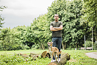 Portrait of serious man with dog in a park - MOEF00162