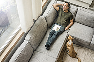 Man at home with tablet on the couch with dog beside him - MOEF00168