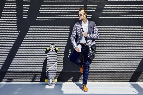 Businessman with longboard and coffee leaning against wall - BSZF00001