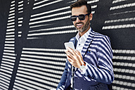 Businessman wearing sunglasses using phone near concrete wall - BSZF00004