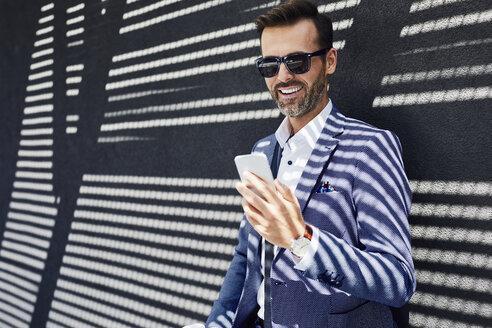 Businessman wearing sunglasses using phone near concrete wall - BSZF00004