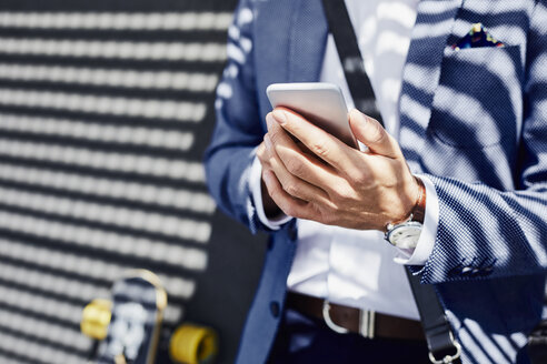 Close-up of businessman holding phone outdoors - BSZF00007