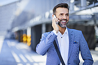 Businessman talking on the phone in the city - BSZF00013