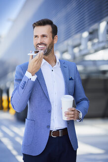 Portrait of smiling businessman with phone and coffee in the city - BSZF00016
