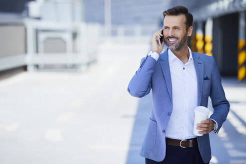 Businessman with coffee talking on phone in the city - BSZF00019