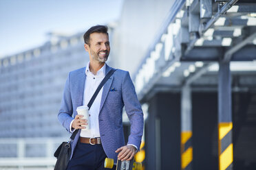 Portrait of businessman with longboard and coffee in the city - BSZF00022
