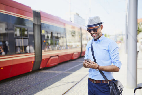 Traveler in the city using cell phone at tram stop - BSZF00028