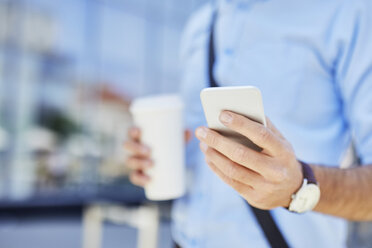 Close-up of businessman using smartphone outdoors - BSZF00031