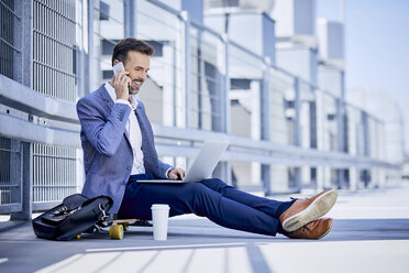 Businessman making phone call and using laptop outdoors - BSZF00040