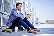 Businessman sitting on longboard and using phone - BSZF00043