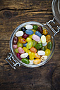 Glass of colourful sweet jellybeans on dark wood - LVF06300