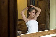 Woman looking in bathroom mirror - ZOCF00502