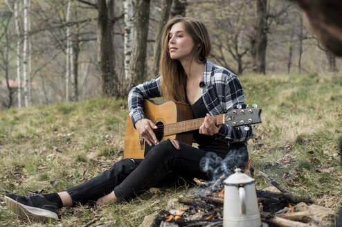 Woman playing guitar in forest at campfire - ZOCF00511