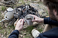 Man drinking coffee at campfire - ZOCF00514