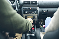 Couple in car with small dog looking at camera - DAPF00804