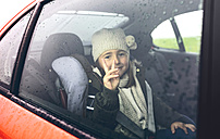 Portrait of happy little girl with wool cap doing victory sign while travelling in car - DAPF00813