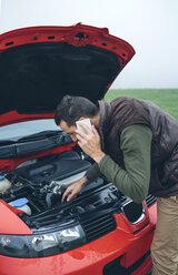 Man on cell phone looking at broken engine car - DAPF00819