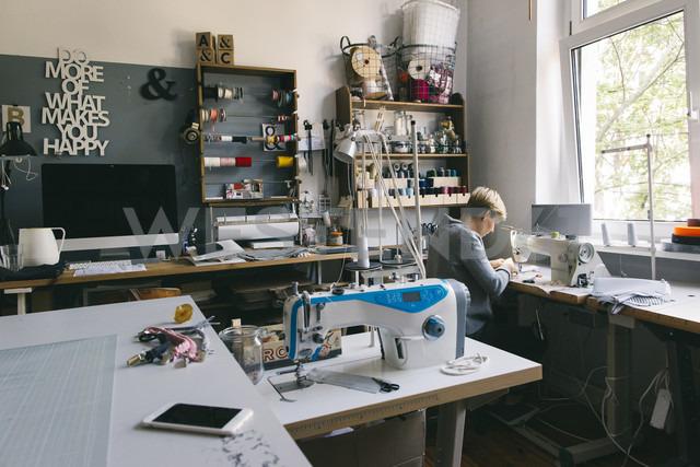 Woman using sewing machine in studio - JUBF00286
