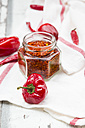 Glass of chili flakes and red chili pods on kitchen towel - LVF06307