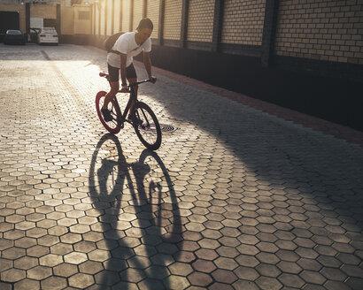 Young man riding fixie bike on backyard at sunset - VPIF00184