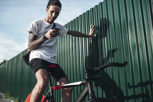 Young man using cell phone on fixie bike - VPIF00187