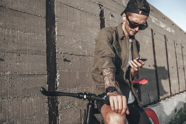 Young man using cell phone on fixie bike - VPIF00190