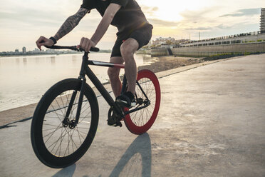 Young man riding fixie bike at the waterfront at sunset - VPIF00193