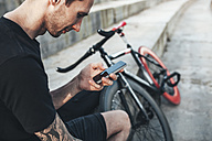 Young man sitting next to fixie bike using cell phone - VPIF00199