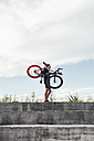 Young man carrying fixie bike on concrete steps - VPIF00202