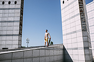 Young man with longboard surrounded by modern architecture - VPIF00205