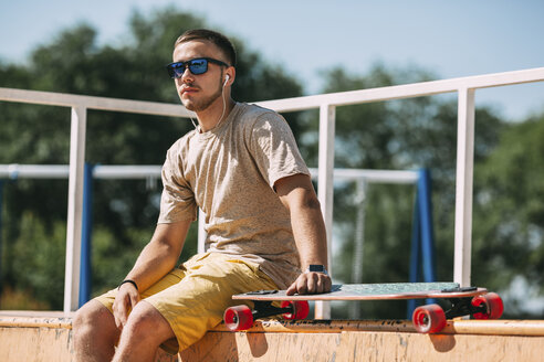 Young man with earbuds and longboard sitting in skatepark - VPIF00214