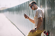 Young man with cell phone and earbuds leaning against a wall - VPIF00220