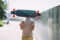 Obscured young man throwing longboard in the air - VPIF00223