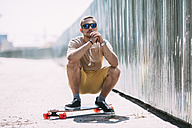Young man crouching on longboard - VPIF00226