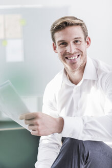 Portrait of smiling businessman in office holding documents - UUF11835