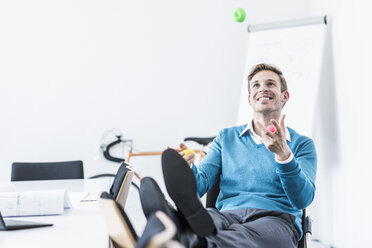 Smiling businessman juggling with balls in office - UUF11841