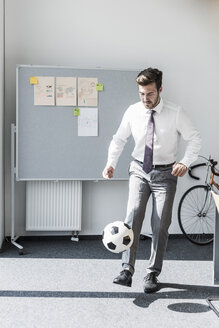 Businessman playing football in office - UUF11850