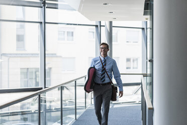 Happy businessman carrying surfboard in office - UUF11880