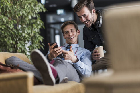 Two colleagues sharing cell phone in office lounge - UUF11898